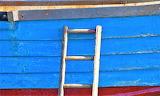Wooden ladder propped against side of boat