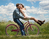 Couple kissing on bicycle