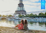 Two women on the left bank of the River Seine watching yachts go