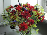^ Velvety red Dahlias arranged with black Scabious, blue Veronic