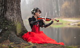 Girl plays violin on the river bank