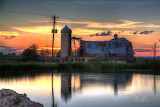 Barn farm silo pond at sunset