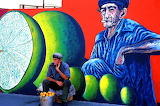 Cuban man in front of mural painting