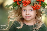 beautiful little girl with a currant wreath