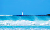 Ocean Waves Spray and Lighthouse on Island