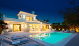 Luxury white villa, pool and garden at night