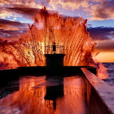 Waves crashing on rocks lighthouse at sunrise