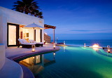 Poolside and ocean view villa at night