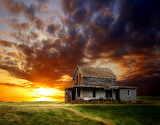 Old ruined house on the background of the sunset