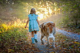 Little girl with dog walking in the woods