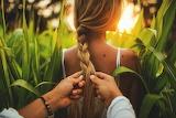 man braiding girl's hair