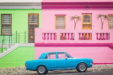 Blue car in fron of pink and green houses