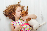 Little girl hugs and kisses her puppy