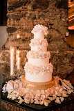 A four-tiered wedding cake with white cream and gold flowers - l