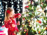 Child-decorating-Christmas-tree-in-family-living-room-with-firep