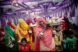 Women sing traditional marital songs at a village wedding India