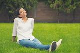 Chica sonriente sentada en el césped