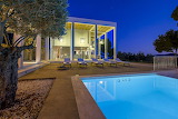 Modern white villa, pool and terrace at night