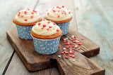 Three cupcakes with cream decorated with hearts