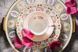 Teacup, saucer and rose petals
