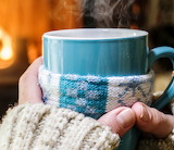 Warming and relaxing near fireplace with a cup of hot drink