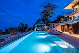 Modern seaview villa and pool at night
