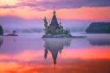 Orthodox church in the fog on islet in the lake