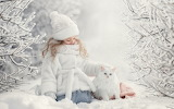 Little girl with a white cat in the snow