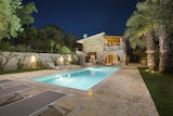 Modern stone villa, pool and garden at night in Corfu