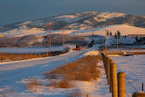 Snow Plow coming up county road west of Missoula at sunrise
