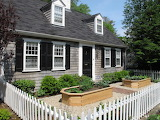 ^ Cottage with picket fence front yard