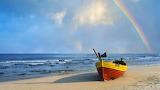 Rainbow over row boat on the beach