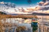 Rowboat, lake, ducks, reeds, village, hills, sky, clouds, landsc