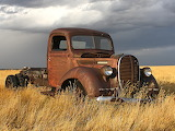 Rusting truck, yellow grass, dark sky.