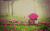 ^ Young couple sitting under umbrella