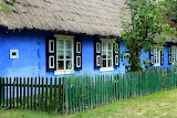 Blue wooden cottage, thatched roof, fence, tree