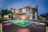 Luxury modern villa, garden and pool at sunset