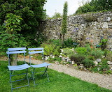 Chairs stone wall pebble path garden Saint-Valéry-sur-Somme Fran