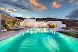 Luxury white hillside villa at dusk in Mykonos