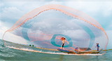 Casting colorful fishing net from boat