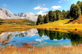 Dolomites-mountains-pond-reflection-meadows-landscape