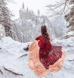 The girl sitting in the snow admires the castle