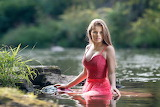 Beautiful blonde girl takes a bath in the river