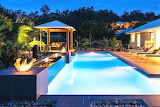 Luxury resort style villa, pool, terrace, and fire pit at night