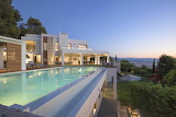 Luxury modern villa, garden and pool at sunset in Crete