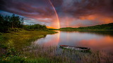 Sunset-rainbow-after-rain-lake-boat-forest-trees-sky-with-red-cl