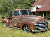Rusty Chevy pickup and rusting house