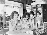 Flappers drinking milkshakes at a soda fountain