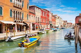 Colorful-houses-and-canal-with-boats-on-murano-island-venice-ita