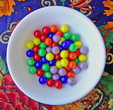 Bright marbles in white bowl